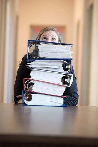 Overwhelmed Woman Behind Stack of 3 Ring Binders